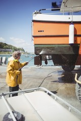 Man cleaning boat with pressure washer