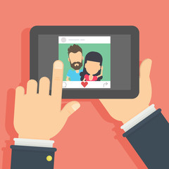 Couple on the screen. Hand holding mobile phone with photo of the couple. Concept of applications or social networks. Like button.