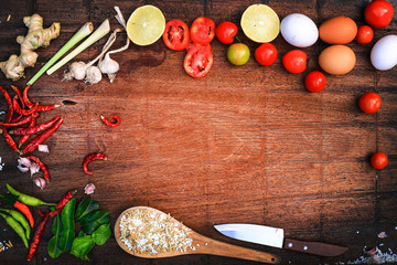 Asian food on the wood background thailand kitchen food. Cooking original eastern top view, wood background texture ,chilli,red tomato, ginger,fish,knife, lemon, onion, bergamot, egg and various.