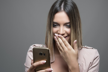 Gorgeous beauty reading message on mobile phone and laughing while covering mouth.
