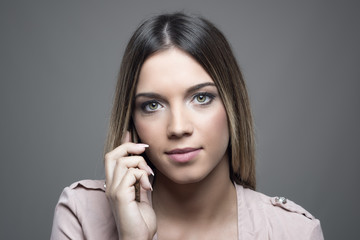Close up portrait of confident serious woman talking on the cellphone looking at camera