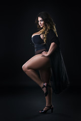 Young beautiful plus size model in underwear, xxl woman on black background