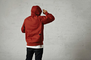 Back shot of a man in black jeans, white t-shirt and red parka putting on his hood against white wall background