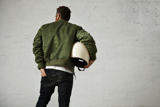 A man in khaki bomber jacket with a motorcycle helmet under his arm reaches into the back pocket of his skinny black jeans, back shot