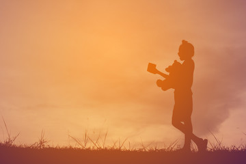 Silhouette a girl with teddy bear on mountain and sky sunset, happy girl in holiday process style vintage tone