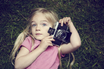 Portrait of little girl taking picture using vintage old retro film camera, lying on grass background