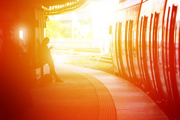 Outdoors train station platform, woman using phone in silhouette
