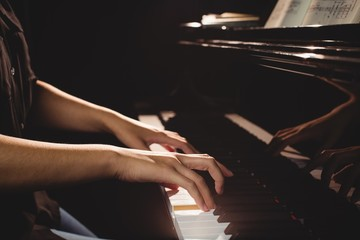 Mid-section of female student playing piano