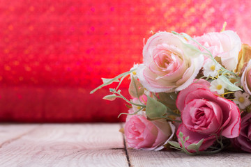 Fake roses,Plastic roses on wood red background