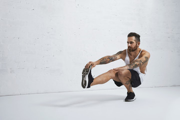 Brutal tattooed calisthenics coach shows exercise moves one leg squat, isolated on white brick wall