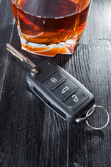 Car key and whiskey alcohol drink in a glass on black wooden table. Don't drink and drive abstract concept.
