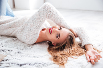 Blonde woman with red lipstick lying on the floor indoors
