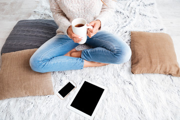 Woman with blank screen tablet and smartphone indoors