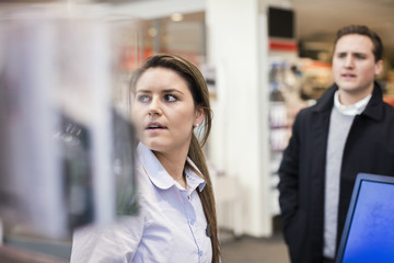 Saleswoman and male customer at cash counter in electronics store