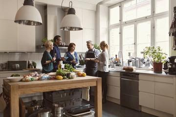 Friends standing at kitchen
