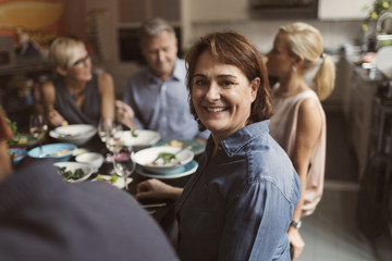 Portrait of happy mature woman sitting with friends at table