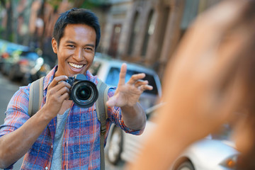 Young man taking picture of model in the street