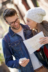 Trendy couple using smartphone and city map of New York on their journey