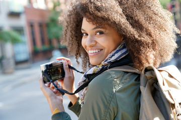 Trendy girl in New York City taking pictures with camera