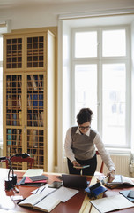 Female lawyer holding book while standing at table in library