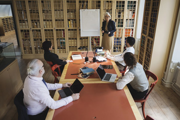 High angle view of senior lawyer giving presentation to coworkers in board room