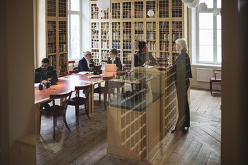 Lawyers working in library seen through glass in library