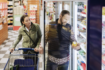 Couple buying groceries while standing by refrigerator in supermarket