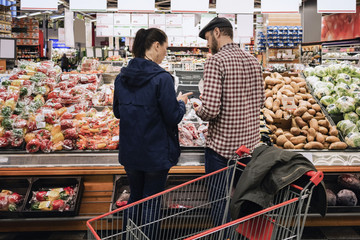 Rear view of couple choosing vegetables while standing at supermarket