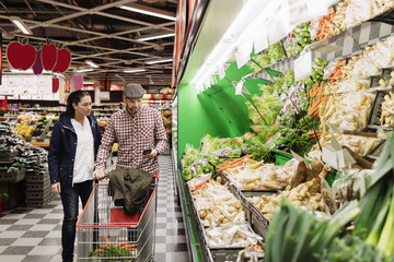 Couple choosing vegetables while using phone in supermarket