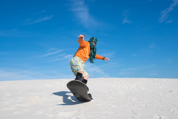 Snowboarder, wearing a scarf is making a trick in a sand desert