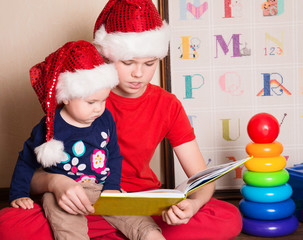 Children in Santa hats reading a Christmas book. Big brother reading
