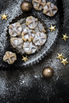 Kleine Belgische Waffeln mit Sternen und Christbaumkugeln auf einem alten Metalluntergrund