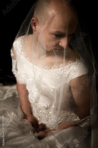 Mann im Brautkleid sitzend