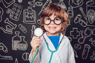 Happy little boy in doctor costume holding sthetoscope on dark background with pattern. The child has glasses