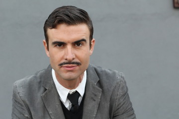 Flamboyant serious retro man with mustache over gray background with copy space