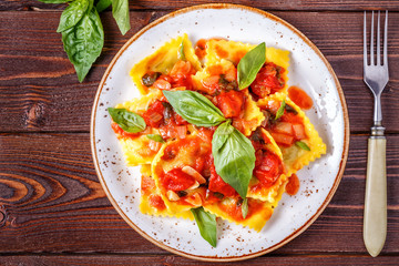 Ravioli with tomato sauce and basil on dark background.