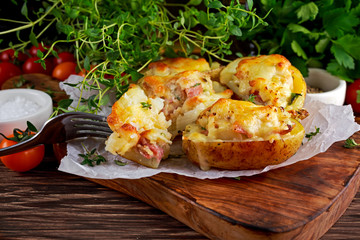 Hot Baked stuffed Potato with cheese, bacon, parsley on wooden table.