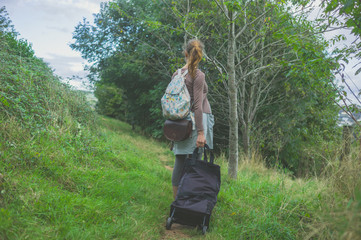 Woman with luggage in the country