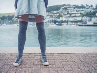 Legs of young woman by river in town