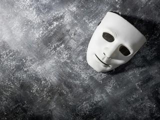 White mask on gray grunge background.