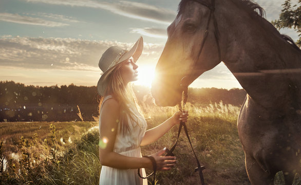 Cheerful, attractive woman with a majestic horse