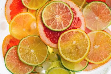 Lime, lemon, grapefruit and oranges with water