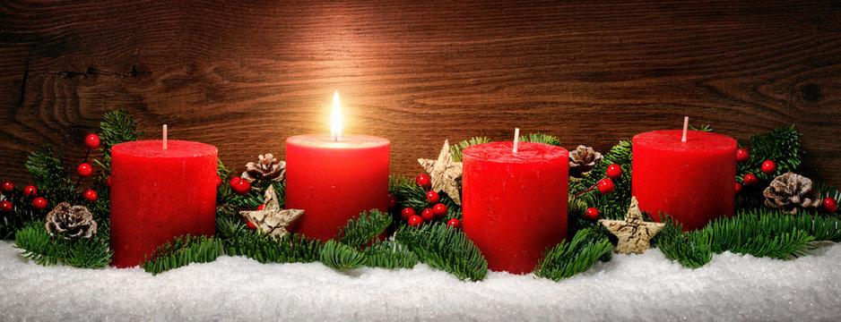 Advent Dekoration mit einer Kerzenflamme, Schnee, Tannenzweigen und Holz Hintergrund