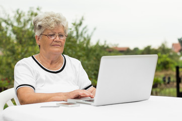 Elderly woman with laptop using internet at home
