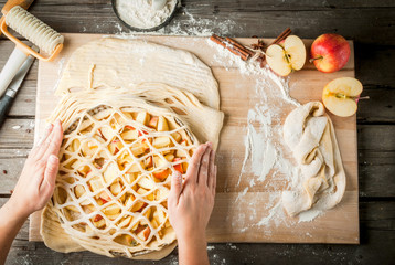 Cooking apple pie, kitchen wooden table, the girl (his hands in the picture) decorates the cake, top view