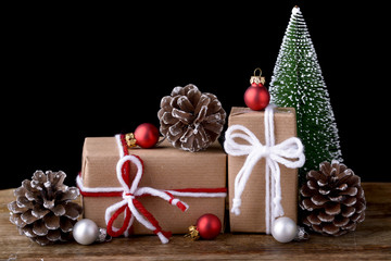 christmas gift box with christmas tree christmas balls and three pine cone on wood