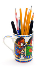 A modern mug full of pens and pencils isolated on white.