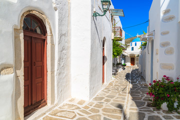 Street in Parikia town with church in distance on Paros island, Greece