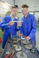 Engineers assessing parts in workshop