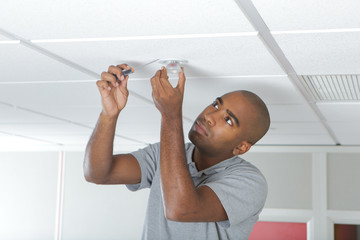 Man fitting spotlight to ceiling